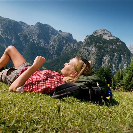 Wanderin entspannt auf Almwiese
