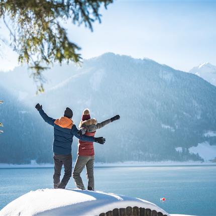 Pärchen in verschneiter Winterlandschaft am See